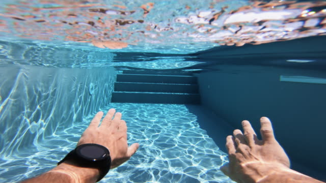 Man swimming POV in a swimming pool: summer relax in Italy