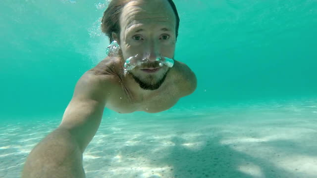 Man swimming in slow motion under water video