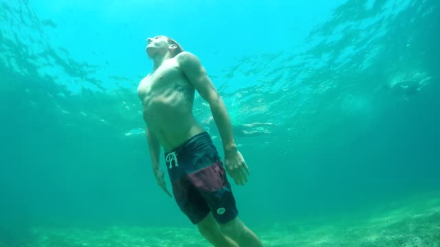 SLOW MOTION UNDERWATER: Man swimming in the ocean, coming to the surface for air video