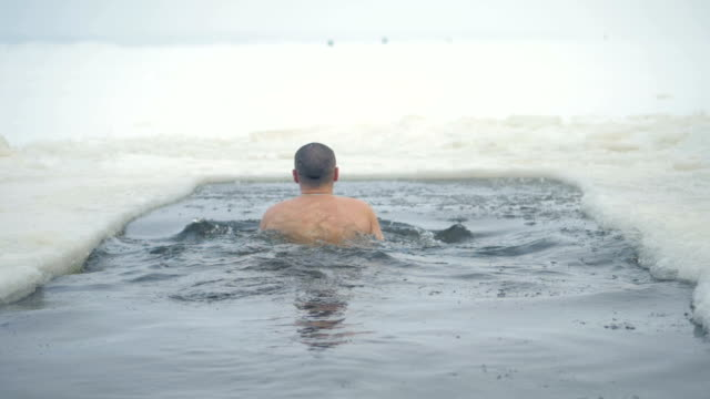 A man swims in a frozen river during snowfall. A back view on a man swimming inside an ice hole under the falling snow. ice stock videos & royalty-free footage