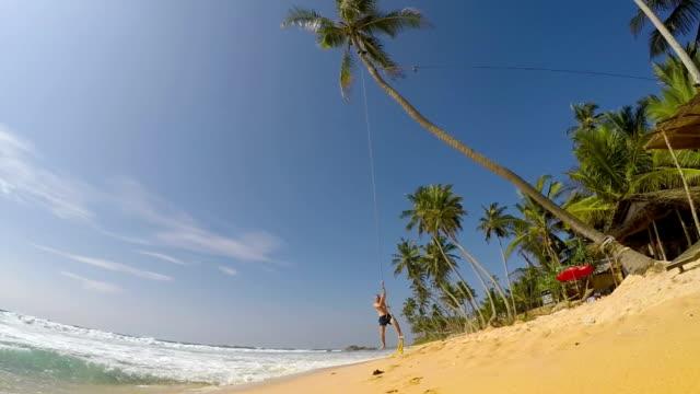 Man swinging on palm tree Man swinging on bungee on beautiful beach on sunny day sri lanka stock videos & royalty-free footage