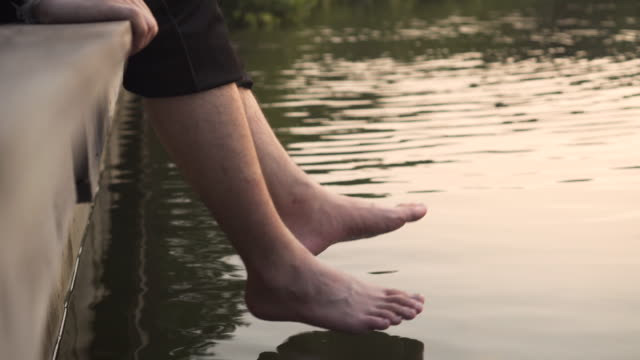 A man swinging with his barefeet over a waterfront. sunset feeling.