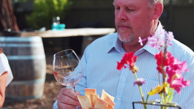 man swirling rosé wine in glass - slow motion - garden party stock videos and b-roll footage