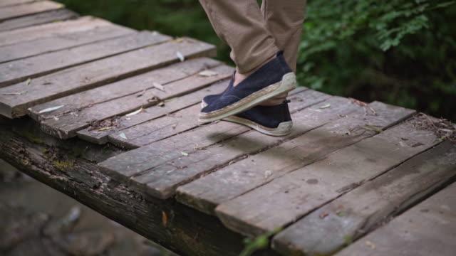 Man take walk on wooden bridge