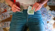 istock Man takes a bag of marijuana and a banknote of 100 euros from his pants pocket. 1249237974