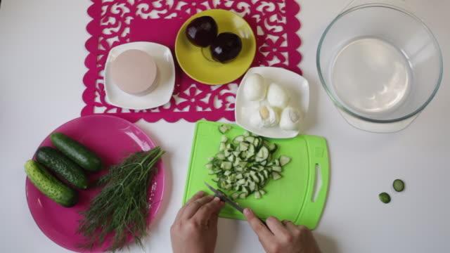 stockvideo's en b-roll-footage met een man neemt een komkommer uit een plaat, en begint op een snijplank te snijden. in de buurt in de gerechten zijn andere ingrediënten voor het koken van suikerbieten, kippenei, worst en dille. bekijk van bovenaf. - venkel