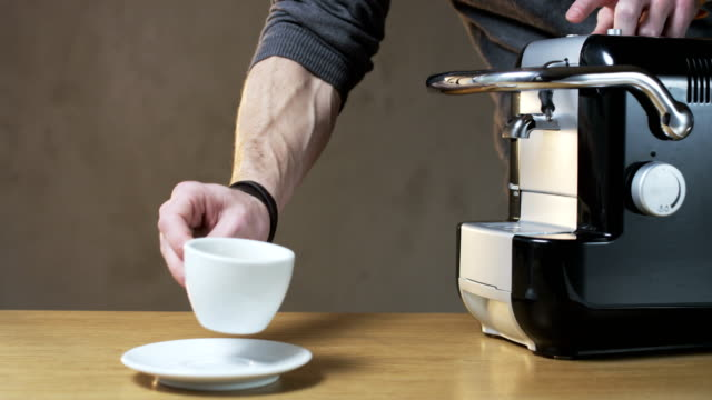 a man takes a cup out of the coffee machine - piattino video stock e b–roll