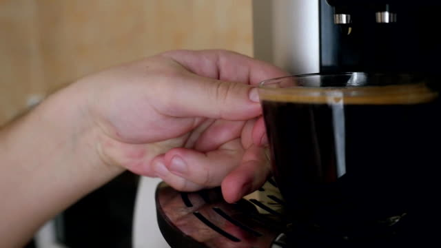 man takes a ready cup of coffee and drinks it with enjoy at home in the morning. Slowmotion video