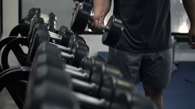 Man takes dumbbell in gym.Closeup of dumbbells row