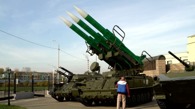 Man takes foto on the smartphone self-propelled launch system of the anti-aircraft missile system A man takes pictures on the smartphone self-propelled launch system of the anti-aircraft missile system nuclear missile stock videos & royalty-free footage
