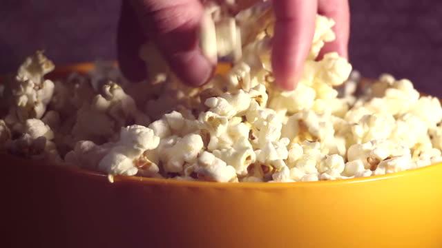 vídeos de stock, filmes e b-roll de um homem pega pipoca quente fresca de uma tigela. um macho pega pipoca de um balde. um homem pega pipoca de um balde enquanto assiste tv. - balde pipoca