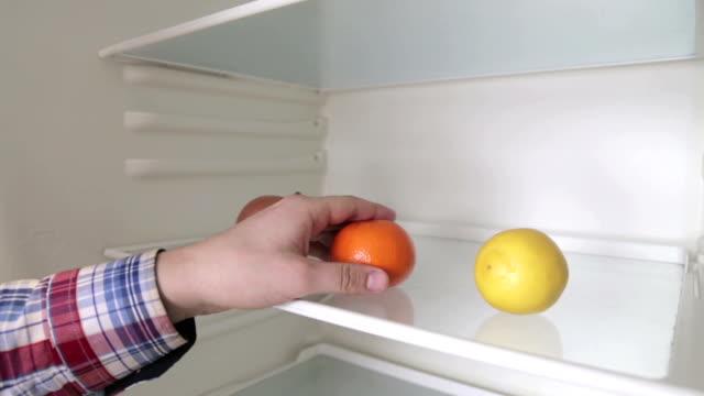 vídeos de stock, filmes e b-roll de um homem leva de mandarim a geladeira - dieta paleo