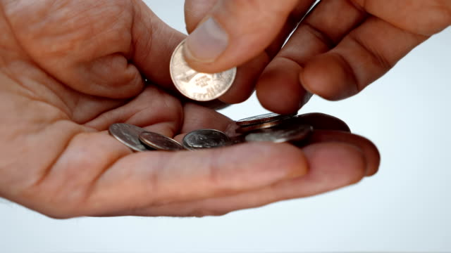 A man takes his time examining a trifle in his hand, trying to find a right coin A man takes his time examining a trifle in his hand, trying to find a coin of the desired denomination. Macro. Closeup. Shallow depth of field. The camera moves around us coin stock videos & royalty-free footage