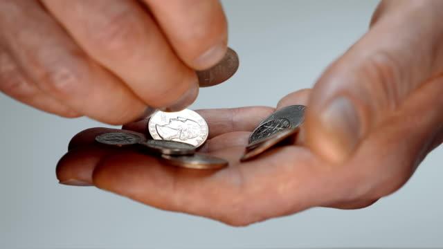 ein mann nimmt sich zeit, eine kleinigkeit in der hand zu prüfen, und versucht, eine richtige münze zu finden - amerikanische geldmünze stock-videos und b-roll-filmmaterial