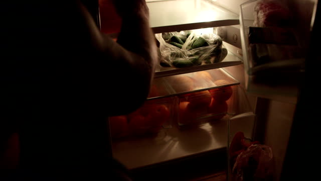 Man takes out food from the fridge at night Man takes out food from the fridge at night snack stock videos & royalty-free footage