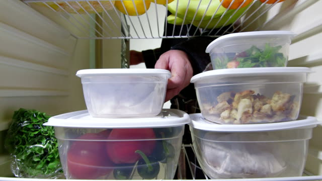 DOLLY: Man takes out stack of food from fridge Man takes out stack of food plastic containers from fridge, view from inside dolly shot fridge stock videos & royalty-free footage
