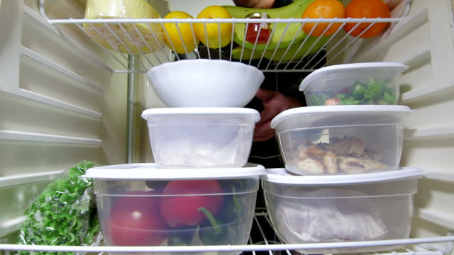 Man takes out stack of food plastic containers from fridge video