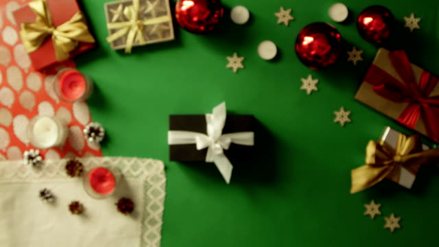 Man takes photo of his Christmas present on smartphone camera on decorated table with chroma key, top down shot video