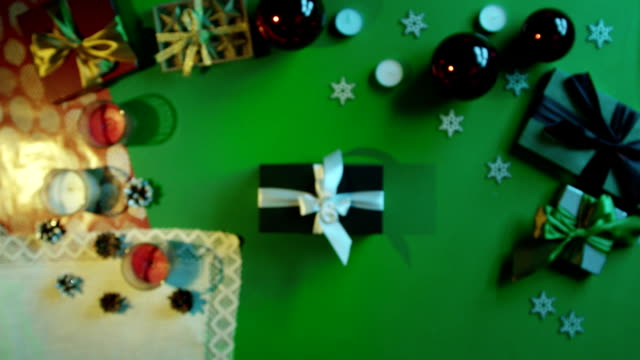 Man takes photo of his New Year present on smartphone camera on decorated table with chroma key, top down shot video