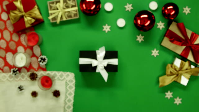 Man takes photo of his Xmas present on smartphone camera on decorated table with chroma key, top down shot video