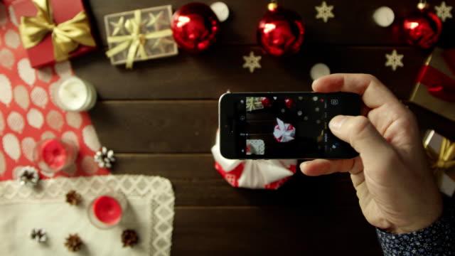 男は彼のクリスマス プレゼントの装飾クリスマス テーブル、上下にショットをスマート フォンのカメラで撮影します。 ビデオ