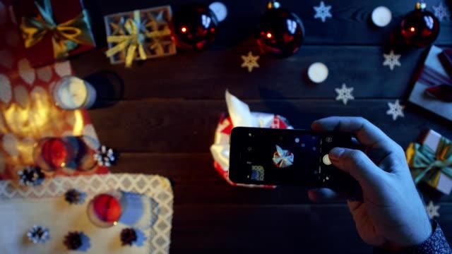 男は現在彼の新しい年の装飾クリスマス テーブル、上下にショットをスマート フォンのカメラで撮影します。 ビデオ