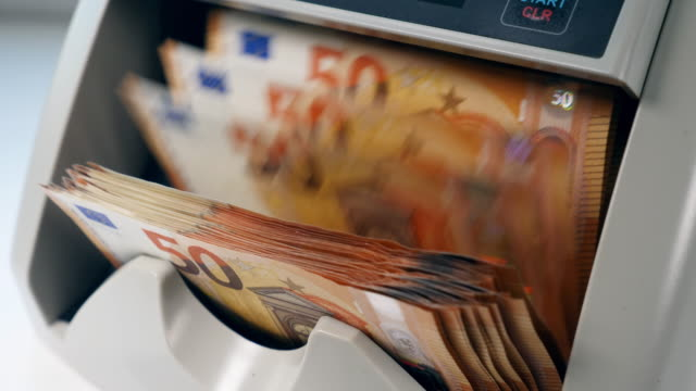 man takes printed euros from a counting machine after checking. - valuta dell'unione europea video stock e b–roll