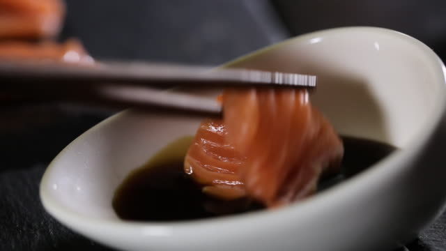 vídeos de stock, filmes e b-roll de homem leva salmão de peixe vermelho com chopstic - comida salgada
