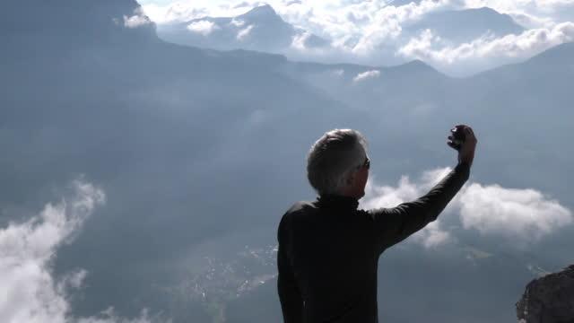 vídeos y material grabado en eventos de stock de hombre toma selfie en cima de la montaña - memorial day weekend