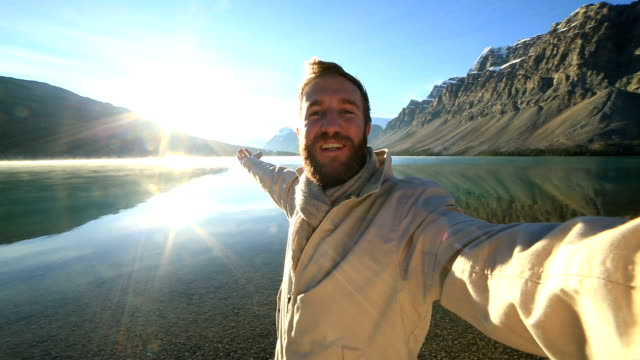 man takes selfie portrait with gorgeous mountain scenery - canada travel stock videos and b-roll footage