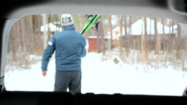stockvideo's en b-roll-footage met een man neemt ski's uit de kofferbak van een auto. - sportartikelen