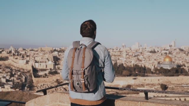 Man takes smartphone photos in Israel, Jerusalem. European tourist male enjoys ancient scenery. Travel. Slow motion video