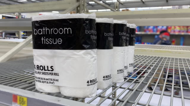 Man Takes Toilet Paper from Shelf of Department Store