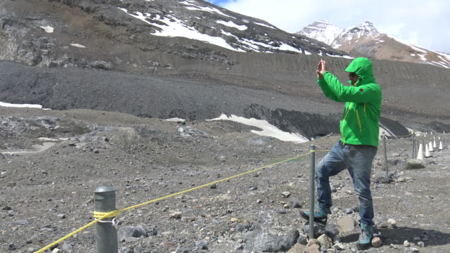 Man taking a photo of Athabasca Glacier video