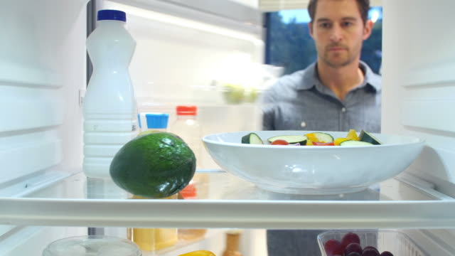 Man Taking Bottle Of Milk From The Fridge Man opens door of refrigerator and takes out bottle of milk before closing door again. Shot on Sony FS700 at a frame rate of 25 fps fridge stock videos & royalty-free footage