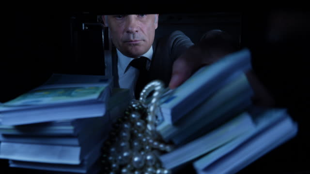 pov man taking euros and jewellery out of a safe - avidità video stock e b–roll