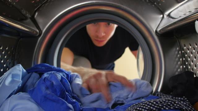 człowiek biorąc usługi pralni z pralka - rozładowywać filmów i materiałów b-roll
