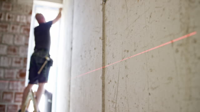 Man taking measurement of a room in a house being renovated