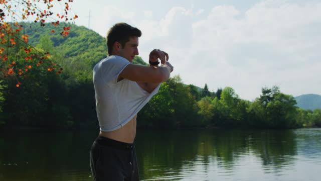 Man taking off his t-shirt Young man taking off his t-shirt. shirt stock videos & royalty-free footage