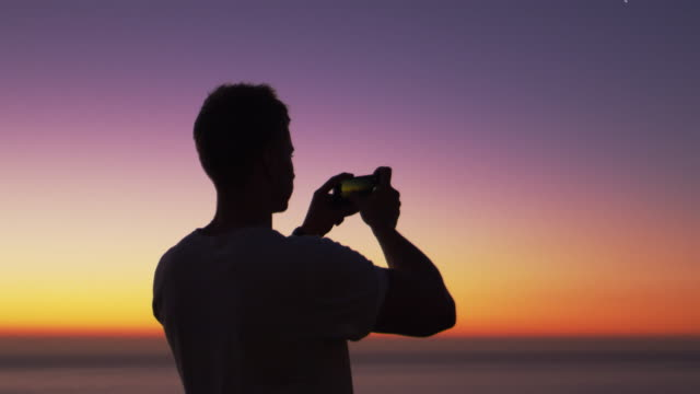 Man taking panorama photo with phone on a beach at sunset video