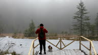 istock Man taking photo of the beautiful frozen mountain lake in the pine forest walking with his dog 1292128605