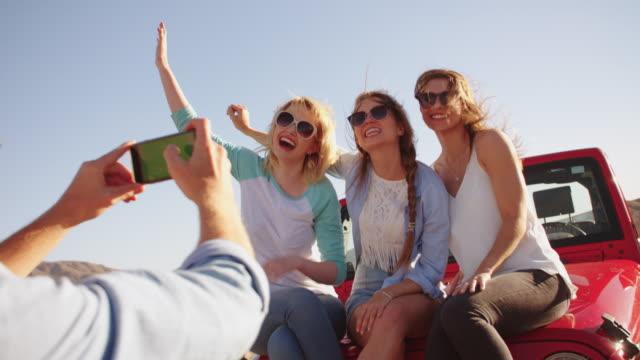 vidéos et rushes de homme prenant photo de trois femmes en voyage photo sur r3d - homme faire coucou voiture
