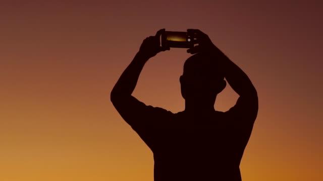 man taking photo sunset. - fotografare video stock e b–roll