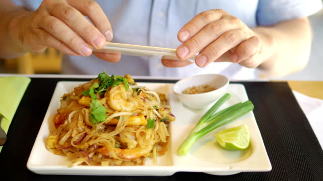 Mann unter Bild des Pad thai Gericht im Reastaurant in 4 k-Slow-Motion 60fps – Video