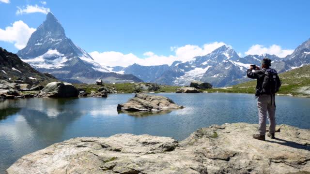 vidéos et rushes de homme prenant des photos de montagne et de paysage avec le téléphone intelligent mobile-modèle libéré - prise avec un appareil mobile