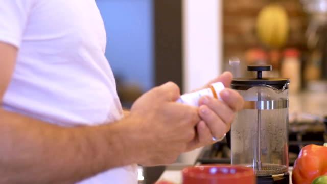男の台所で薬の規定のびんから錠剤の薬を服用 - 処方箋点の映像素材/bロール