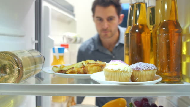 Man Taking Plate Of Iced Cupcakes From The Fridge Man opens door of refrigerator and takes out plate of iced cupcakes before closing door again. Shot on Sony FS700 at a frame rate of 25 fps fridge stock videos & royalty-free footage