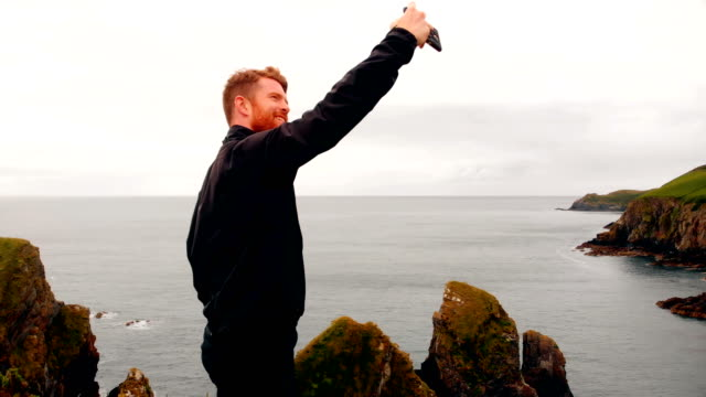 Man taking selfie from mobile phone on cliff 4k Young man taking selfie from mobile phone on cliff 4k mid adult stock videos & royalty-free footage