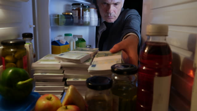 pov man taking stacks of euros out of a fridge - avidità video stock e b–roll
