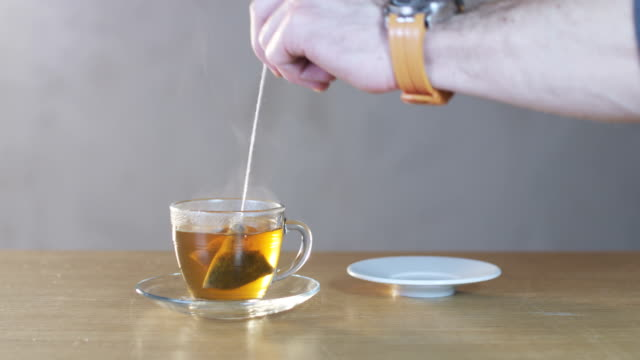 man taking teabag out of a cup - piattino video stock e b–roll